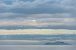 Inchkeith island shrouded in mist this morning in the Firth of Forth as an early morning plane approaches Edinburgh airport.<br /> © Jon Davey/ EEm