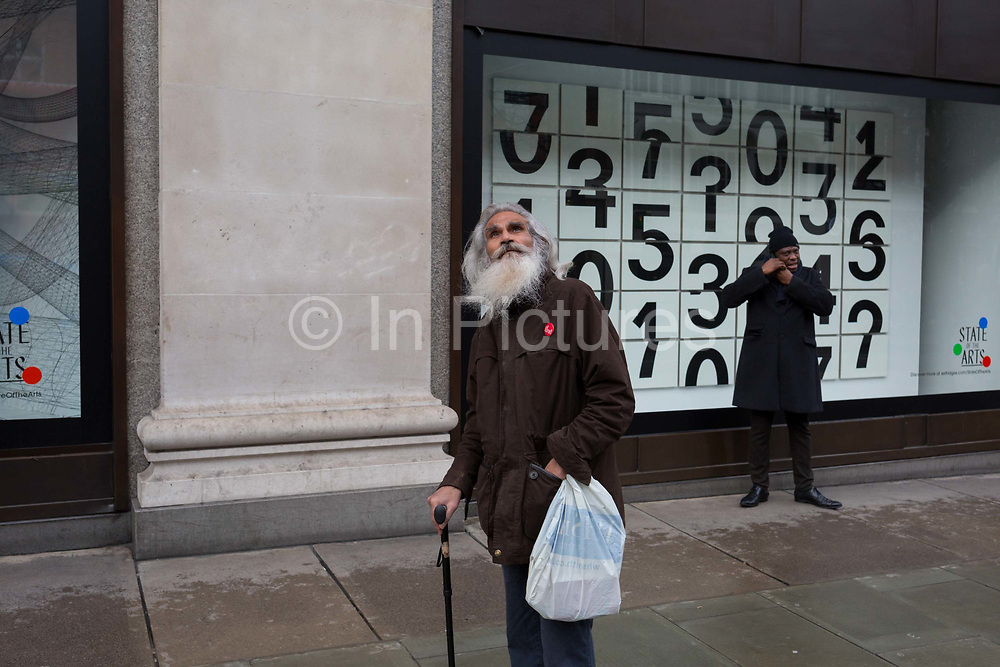 Shoppers walk past a window display that features numbers - part of a design theme called State of the Arts, at the Selfridges department store on Oxford Street, on 4th March 2019, in London England. Darren Almonds piece 'Chance Encounter 004', consists of a grid formed from rectangular panels, featuring fragmented numbers that appear to scroll across the surface. <br /> State of the Arts is a gallery of works by nine crtically-acclaimed artists in Selfridges windows to celebrate the power of public art. Each of the artists are involved in creating a site-specific artwork at one of the new Elizabeth line stations as part of the Crossrail Art Programme.