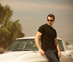 sexy man in Ray Bans and a black tee shirt leaning against a beautiful white Corvette in Florida
