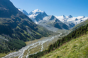 """The icy Bernina Range rises above Ova da Roseg river valley, near Pontresina, Switzerland, in the Bernina Alps, Europe. Tschierva Glacier flows from the peaks clustered on left: Piz Scerscen (3971 m) and Piz Roseg (3937 m/12,917 ft). At right (west), Roseg Glacier flows from Piz Glüschaint (3594 m). Val Roseg is in the Swiss canton of Graubünden (or Grisons / Grigioni / Grischun); the lower Roseg Valley is in Pontresina, whereas the upper valley is in an exclave of Samedan Municipality. Hike from Pontresina up Roseg Valley to Fuorcla Surlej for stunning views of Piz Bernina and Piz Roseg, finishing at Corvatsch Mittelstation Murtel cable car. Walking 14 km, we went up 1100 meters and down 150 m. Optionally shorten the hike to an easy 4 km via round trip lift. The Swiss valley of Engadine translates as the """"garden of the En (or Inn) River"""" (Engadin in German, Engiadina in Romansh, Engadina in Italian), and is part of the Danube basin."""