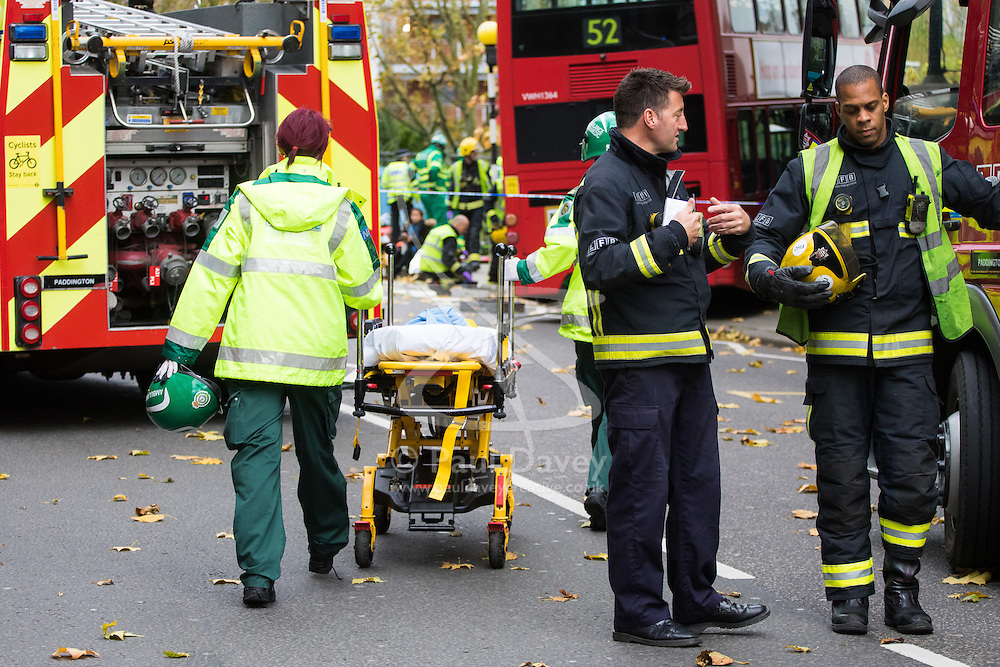 Ladbroke Grove, London, November 17th 2016. A double decker bus crashes into Kensal House on Ladbroke Grove prompting a major response from the emergency services including the air ambulance. According to Detective Chief Superintendent Ellie O'Connor of Met Police Kensington and Chelsea, 14 people including the driver were hurt, with none sustaining life-threatening or life changing injuries. Police officers would not speculate on the cause of the accident, but apologised for delays and commended all branches of the emergency services for their prompt and efficient response. The bus will be towed away for further investigations. PICTURED: A Paramedic pushes a stretcher towards where casualties are being given treatment on the side of the road.