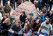 "People gathered listening to speakers. Occupy London protest at St Pauls, October 16th 2011. Protest spreads from the US with this demonstrations in London and other cities worldwide. The 'Occupy' movement is spreading via social media. After four weeks of focus on the Wall Street protest, the campaign against the global banking industry started in the UK this weekend, with the biggest event aiming to ""occupy"" the London Stock Exchange. The protests have been organised on social media pages that between them have picked up more than 15,000 followers. Campaigners gathered outside  at midday before marching the short distance to Paternoster Square, home of the Stock Exchange and other banks.It is one of a series of events planned around the UK as part of a global day of action, with 800-plus protests promised so far worldwide.Paternoster Square is a private development, giving police more powers to not allow protesters or activists inside."