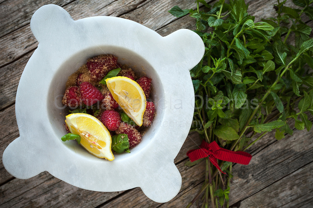 Overhead of mortar with fresh ingredients from the garden: raspberries, lemon in slices and fresh mint, covered with brown sugar.