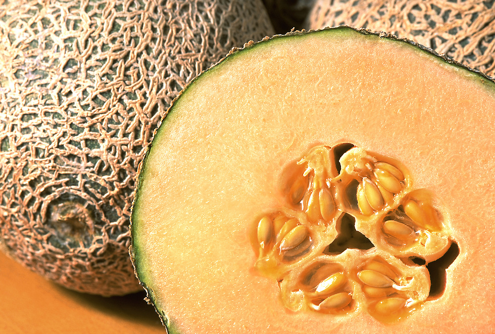 Close up selective focus photograph of a group of Persian melons with one cut open
