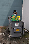 """Humorous photograph of a mime in a garbage dumpster reading a physics text book visually depicting the saying """"A mime (mind) is a terrible things to waste!"""""""