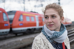 Portrait of a young woman with railway track and red train in the background