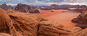 Sandstone mountains rise from the red sand at the entrance to Burrah Canyon, Wadi Rum, Jordan.