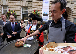 © Licensed to London News Pictures. 19/09/2012. Bristol, UK. Bristol's Lord Mayor Peter Main with Joe Wheatcroft from Source food shop, and the launch of the Bristol Pound, the first local currency to be implemented across a major UK city and already supported by over 300 traders, including electronic payments and supported by the Bristol Credit Union. The notes feature art by local artists and the launch was in Corn Street Bristol, the site of the historic trading area where deals were done on the nails, metal pedestals on the street.  19 September 2012..Photo credit : Simon Chapman/LNP