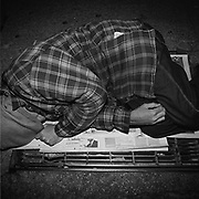 A homeless man sleeps on a grate which serves as the exhaust vent for heating the skyscrapers on at the corner of York Street and Wellington Avenue West located in Toronto's Financial District..(Credit Image: © Louie Palu/ZUMA Press).