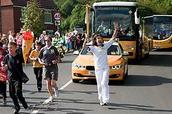 The Olympic Torch relay reaches Sheffield on day 38 coverage from the Chapeltown - Ecclesfield - Parson Cross section of the Journey.<br /> Runner 106 Katharine Morris accompanied by local Children from Ecclesfield School reaches the Junction of  Chapeltown Road/The Common and Church Street in Ecclesfield<br /> 25 June 2012.<br /> Image © Paul David Drabble