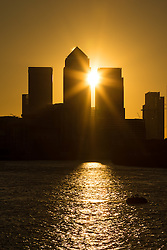 © Licensed to London News Pictures. 05/10/2016. LONDON, UK.  The sun rises behind Canary Wharf and London's financial district this morning, seen from the River Thames. Forecasters are predicting a day of clear and sunny weather in London today.  Photo credit: Vickie Flores/LNP