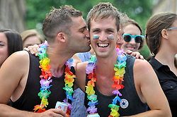 © Licensed to London News Pictures. 08/07/2017. London, UK. Men wearing floral garlands share a kiss.  Tens of thousands of visitors, many wearing eye-catching costumes, gather to watch and take part in the annual Pride in London Parade, the largest celebration of the LGBT+ community in the UK.   Photo credit : Stephen Chung/LNP