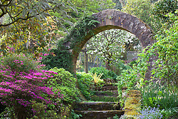 Steps and circular stone arch leading from the main garden to the vegetable garden at Greencombe Gardens, Somerset