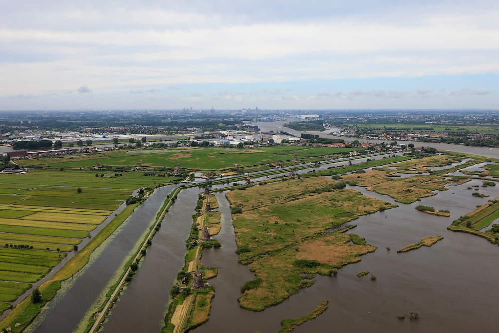 Nederland, Zuid-Holland, Kinderdijk, 22-05-2011; molens aan de hoge en een lage boezem van de polder Nieuw-Lekkerland, onderdeel van de Alblasserwaard. Skyline van Rotterdam aan de horizon..De meervoudige molengang is gebruikt voor het het droogmalen van de polder. Door de bodemdaling in de drooggevallen polders waren uiteindelijk twee waterreservoirs (boezems) nodig om het water in fases uit te slaan (het bemalen) en zo het water in de polder op peil te houden. Het uitgeslagen water wordt bij het dorp Elshout door middel van sluizen geloosd in rivier de Lek (boven in beeld). De watermolens maken deel uit van het werelderfgoed en staan op de Werelderfgoedlijst van de UNESCO..Windmills used for pumping the water out of the nearby polder and maintaining the water level. The mill network at Kinderdijk, with 19 windmills the largest in the Nethelands, is listed on the World Heritage List of Unesco..Skyline Rotterdam at the horizon..luchtfoto (toeslag); aerial photo (additional fee required);.foto Siebe Swart / photo Siebe Swart
