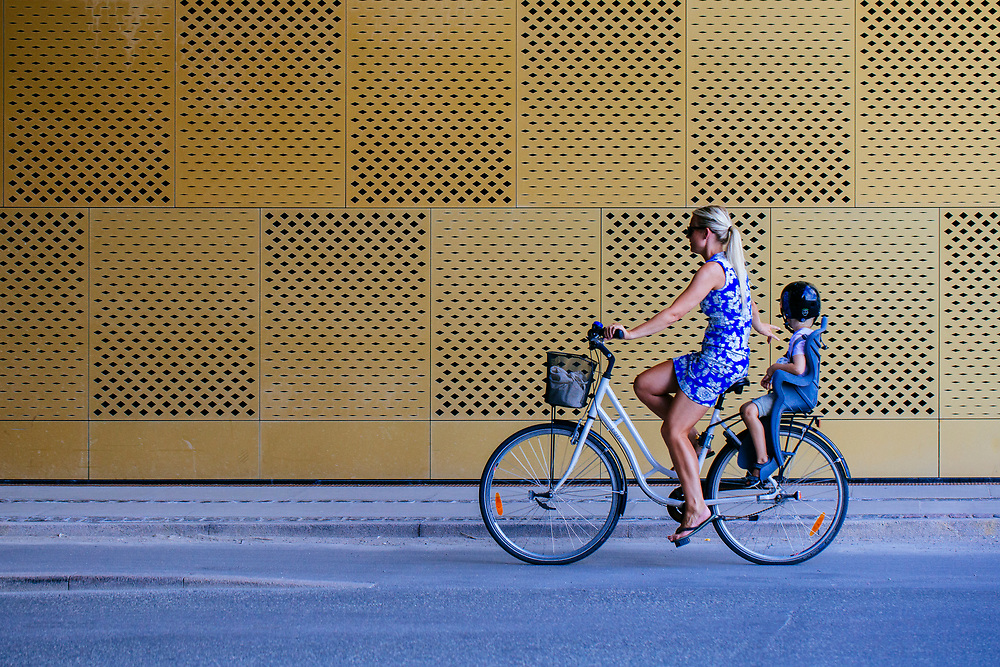 Elegant Blond woman in a blue flowery dress riding a bicycle signalling right with a child on the back of the bike in helmet. <br /> <br /> SELF PROPELLED is portrait study of Copenhagen and its residents.