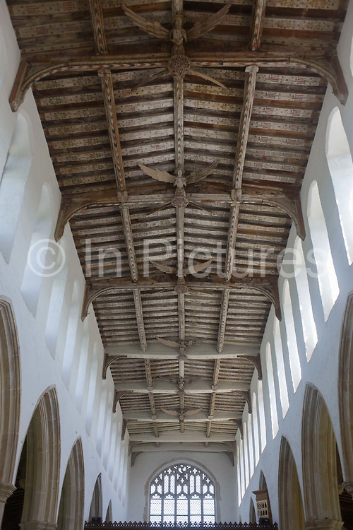 Timbered eaves with inscriptions and carved angels in the roof of Blythburgh church, Suffolk. Over the centuries it was thought that the Parliamentarian William Dowsing shot at the angels during the English civil war, in 1644. <br /> Several of the angels are peppered with lead shot. Here is another of those Suffolk legends; that Dowsing and the churchwardens fired muskets at the angels to try and bring them down. But when the angels were restored in the 1970s, the lead shot removed was found to be 18th century; contemporary with them there is a note in the churchwardens accounts that men were paid for shooting jackdaws living inside the building, so that is probably where the shot arises from.