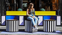 "© Licensed to London News Pictures. 14/09/2019. LONDON, UK.  A woman sits on a sculptural bench as ""Walala Lounge"" opens in Mayfair's South Molton Street.  Artist and designer Camille Walala's installation comprises 10 sculptural benches, accompanied by planters and a series of oversized flags strung, bunting-style, from shopfront to shopfront, converting the street into an immersive corridor of colour as part of this year's London Design Festival.  Photo credit: Stephen Chung/LNP"