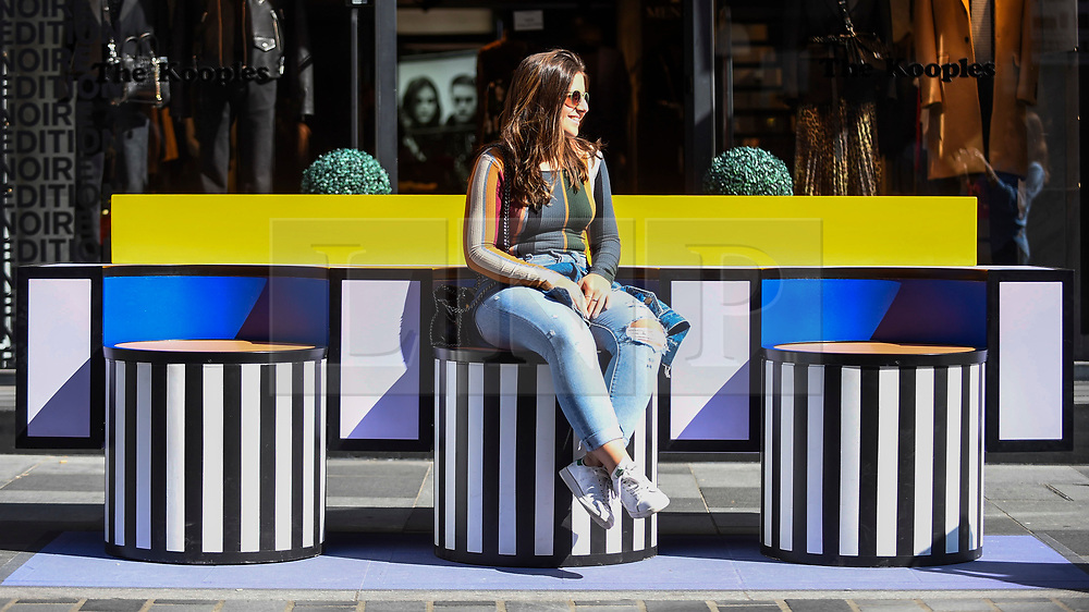 """© Licensed to London News Pictures. 14/09/2019. LONDON, UK.  A woman sits on a sculptural bench as """"Walala Lounge"""" opens in Mayfair's South Molton Street.  Artist and designer Camille Walala's installation comprises 10 sculptural benches, accompanied by planters and a series of oversized flags strung, bunting-style, from shopfront to shopfront, converting the street into an immersive corridor of colour as part of this year's London Design Festival.  Photo credit: Stephen Chung/LNP"""