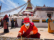 07 MARCH 2017 - KATHMANDU, NEPAL: A monk lights butter lamps on the walkway around Boudhanath Stupa during the consecration ceremony at the stupa. Boudhanath Stupa, the most important Buddhist site in Nepal and a popular tourist attraction, was consecrated Tuesday in a ceremony attended by thousands of Buddhist monks and Buddhist people from Nepal and Tibet. The stupa was badly damaged in the 2015 earthquake that devastated Nepal. The stupa, which reopened in November 2016, was repaired in about 18 months. The repair was financed by private donations raised by international Buddhist organizations.     PHOTO BY JACK KURTZ