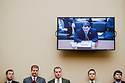 """Congressional staffers look on as Gov. SCOTT WALKER (R-WI) appears on the T.V. monitor as he testifies before a House Oversight and Government Reform Committee Hearing on """"State And Municipal Debt: Tough Choices Ahead."""" The Wisconsin Governor defended his efforts to limit public employees' collective bargaining rights and make them pay more toward pension and health care costs."""