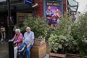 An elderly couple rest on a bench infront of Covent Garden Underground station, and next to a poster advertising the musical, Aladdin, on 15th June 2019, in London, England.