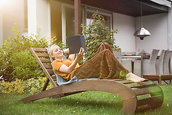 Beautiful young woman reading a book in the domestic garden, Munich, Bavaria, Germany