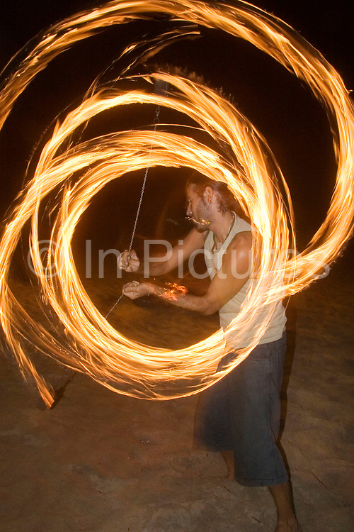 Spanish fire show expert performs on Klong Nin beach, Koh Lanta. Chains with  tightly packed cloth ends are soaked in petrol and lit, while the performer swings them independently, and closely to his body.