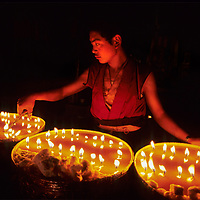 A Tibetan Buddhist monk tends yak butter candles at Tashilumpo Monastery in Shigatse, Tibet, China.