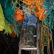 A fisherman inside the loft of his lock-up retrieving new nets to go trawling. Folkestone, Kent, United Kingdom.