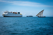 A small sail fishing boat on the sea between the Mapinduzi II passenger and cargo ship and the Bo Yuan, an industrial Chinese fishing boat outside the port of Stone Town and Zanzibar, Tanzania.  (photo by Andrew Aitchison / In pictures via Getty Images)