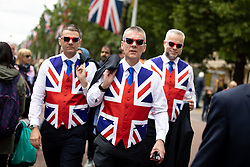 © Licensed to London News Pictures. 08/06/2019. London, UK. Three men dressed in Union Jack flags walk down the Mall after Trooping the Colour, a ceremony to mark Queen Elizabeth II official birthday. Photo credit : Tom Nicholson/LNP