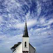 Raukokore's Anglican Church sits on the shore line of the small villiage of Raukokore, a small settlement close to the East Cape in the northeastern North Island of New Zealand. It is located on State Highway 35, close to the mouth of the Raukokore River, 40 kilometres to the west of Hicks Bay..The Anglican church is a landmark of the East Cape region, which stands isolated close to the shore of Papatea Bay.  North Island, New Zealand. 19th January 2010 Photo Tim Clayton