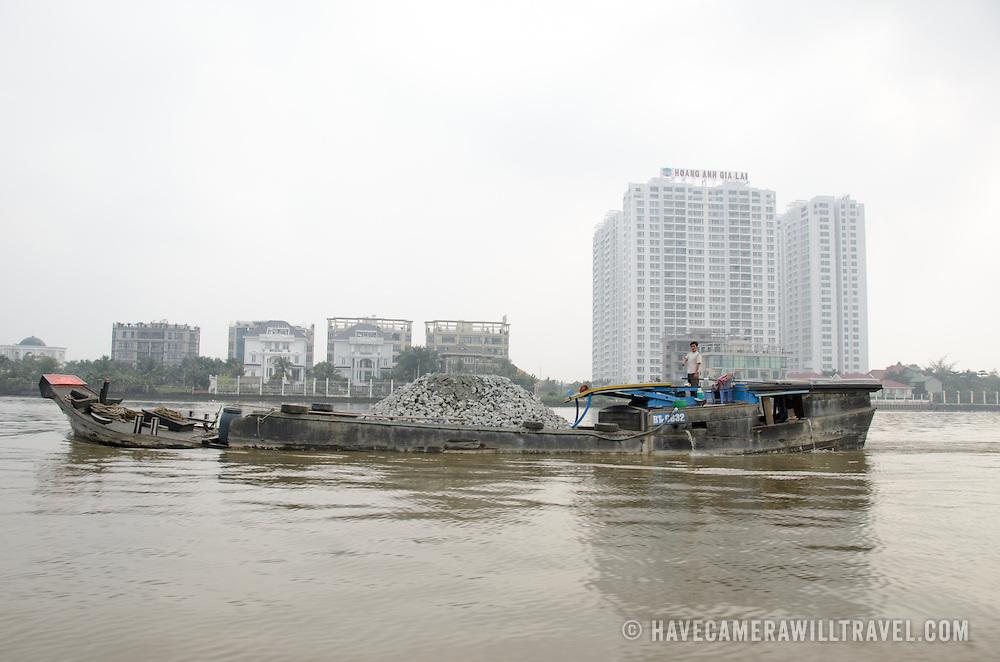 A boat transports broken up concrete along the Saigon River in Ho Chi Minh City, Vietnam.