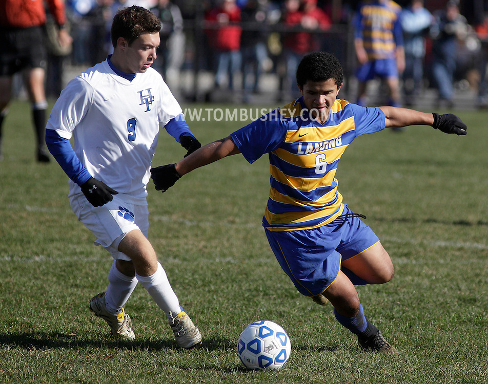 Middletown, New York - Lansing's Ellington Hopkins, right, looks to move the ball past Tyler Rondeau of Hoosick Falls during a Class C state semifinal boys' soccer game at Faller Field in Middletown on Saturday, Nov. 17, 2012.