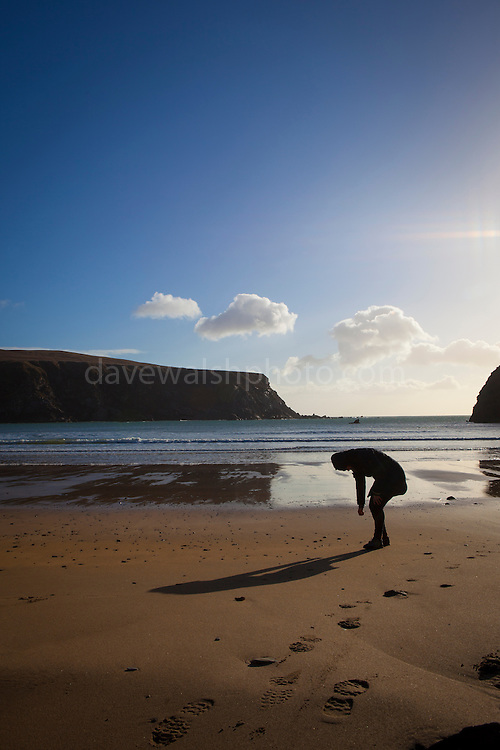 Bending over to pick up stones at Silver Strand, Malin Beg, Donegal, on Ireland's Wild Atlantic Way.