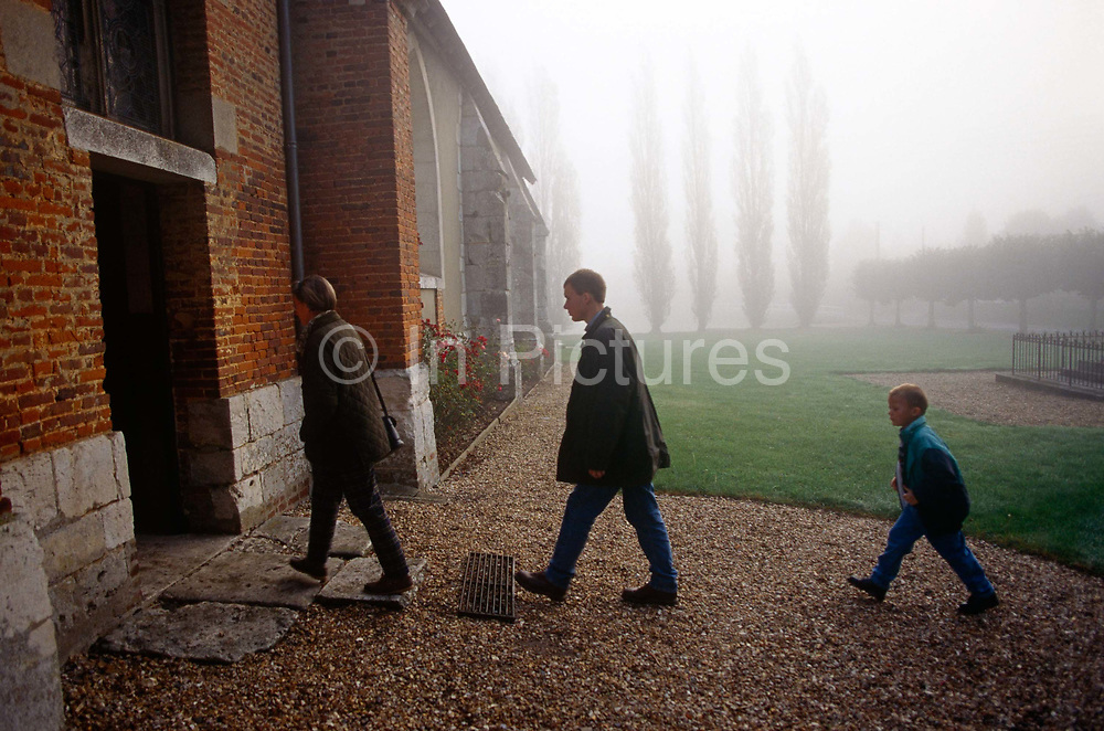 Three members of a French family walk into their local Catholic church at Equetot in rural Normandy early on a misty morning. Led by the mother and father, a young boy walks fast on the church property gravel and on to the large old flagstones that are laid at the 16th century church door entrance. Lingering mist remains in tall popular trees in the distance though the sun is burning through this cold morning. It is estimated that somewhere between 83% to 88% of France's population are Catholic. The church is organised into 98 dioceses, served by 20,523 priests.