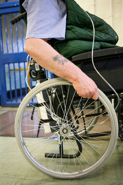 An elderly disabled prisoner who carries a portable oxygen tank wheels along the wing in the vulnerable prisoners unit, which is located on the E wing of the Onslow building at Wandsworth prison. HM Prison Wandsworth is a Category B men's prison at Wandsworth in the London Borough of Wandsworth, South West London, United Kingdom. It is operated by Her Majesty's Prison Service and is one of the largest prisons in the UK with a population over 1500 people.  (photo by Andy Aitchison)