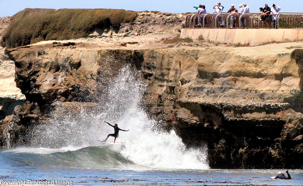 A surfer catches a wave at the legendary Steamer Lane break in Santa Cruz, Califonria as spectators watch from atop the Lighthouse Point cliff.<br /> Photo by Shmuel Thaler <br /> shmuel_thaler@yahoo.com www.shmuelthaler.com