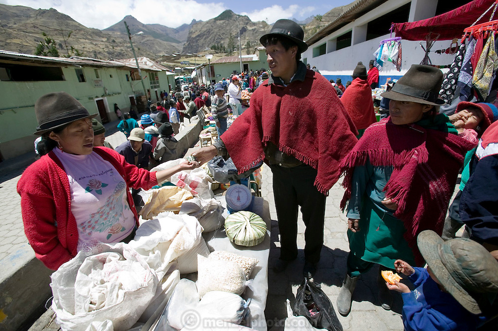 Orlando Ayme, 35, (wearing a red poncho), pays for some flour he bought from a vendor in the weekly market in Simiatug (his wife, Ermalinda is by his side on the right, also with red poncho. His youngest son is on his wife's back and Alvarito, 4 is in the blue sweater eating an orange.) He sold two of his sheep at this weekly market in the indigenous community of Simiatug for $35 US in order to buy potatoes, grain and vegetables for his family. ((Supporting image from the project Hungry Planet: What the World Eats.)