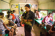 05 JUNE 2014 - YANGON, YANGON REGION, MYANMAR: A woman on the Yangon Circular Train. The Yangon Circular Train is a commuter train that circles Yangon, Myanmar (Rangoon, Burma). The train is 45 kilometers long, makes 38 stops and takes about three hours to make a loop of the city.     PHOTO BY JACK KURTZ