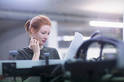 Contemplative young woman reading paper  while standing by printing machinery