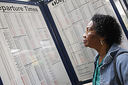 Woman looking at train timetable at railway station,