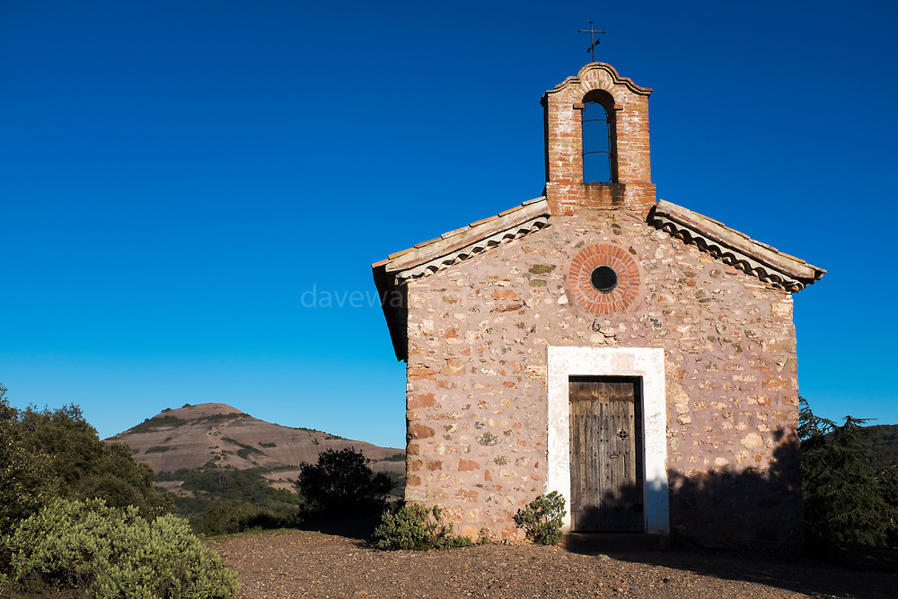 The 15-16th century Chapel of Sant Jaume de la Mata, in Mura, near the Coll d'Estenalles in Parc Natural de Sant Llorenç del Munt i l'Obac, Barcelona, Catalonia, with the peak of Montcau in the background.