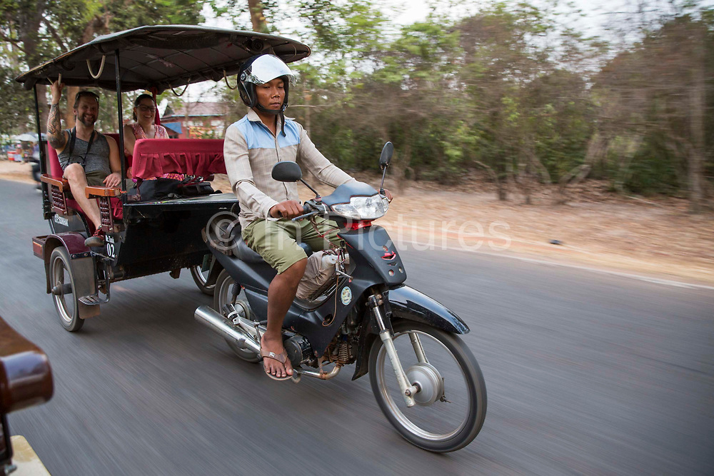 A Cambodian man drives two smiling Western tourists on his a motorbike Tuk Tuk along the road from Angkor region, Siem Reap Province, Cambodia, South East Asia.