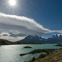 A wind-swept lenticular cloud soars over the Grand Tower of Paine, the Horns of Paine and Pehoe Lake in Torres del Paine National Park, Chile.
