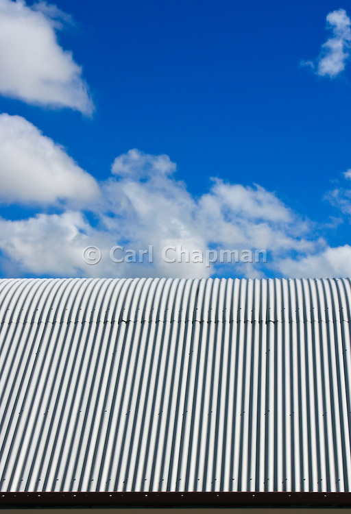 Blue sky and clouds over a corrugated tin roof <br /> <br /> Editions:- Open Edition Print / Stock Image