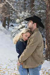 cowboy and a girl wrapped in a blanket outdoors in the snowy woods cowboy and a girl embracing while outdoors in the snowy woods of New Mexico