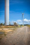 Man walking along a gravel path is dwarfed by wind turbines on a windfarm in Ninh Thuan province, Vietnam<br /> , Southeast Asia
