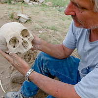 Smithsonian archaeologist & forensics specialist, Dr. Bruno Frohlich, examines a bronze-age skull at an archaeology site above the Delger River near Muren, Mongolia. This  may be 2700+ years old.