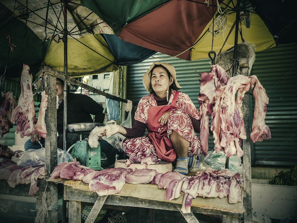 People selling meat at Phsar Leu Thom Thmey market in Siem Reap Cambodia. This is one of the largest public markets of the city. Hundreds of market stalls inside the building and outside of it sell their goods everyday to local residents.